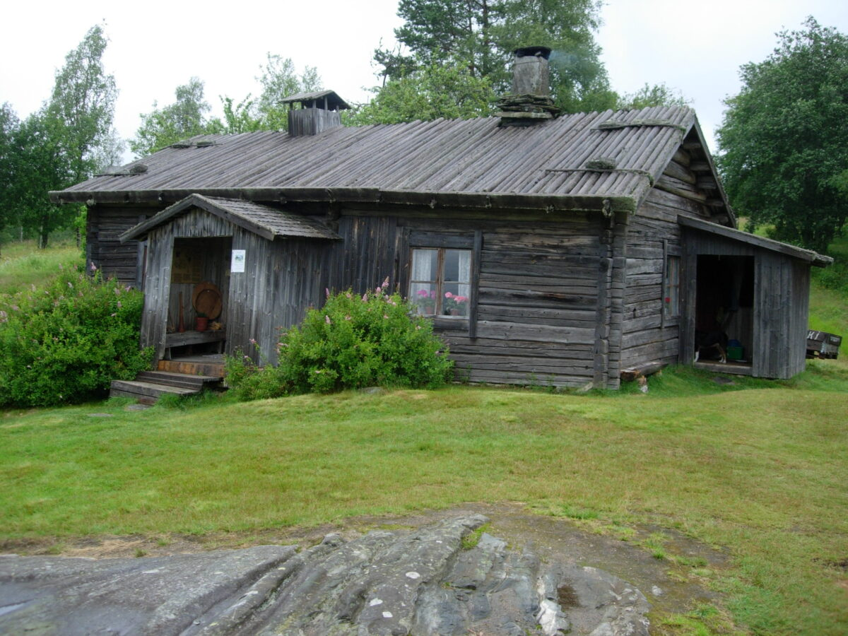 gammal, grå torpbyggnad på grön gräsmatta