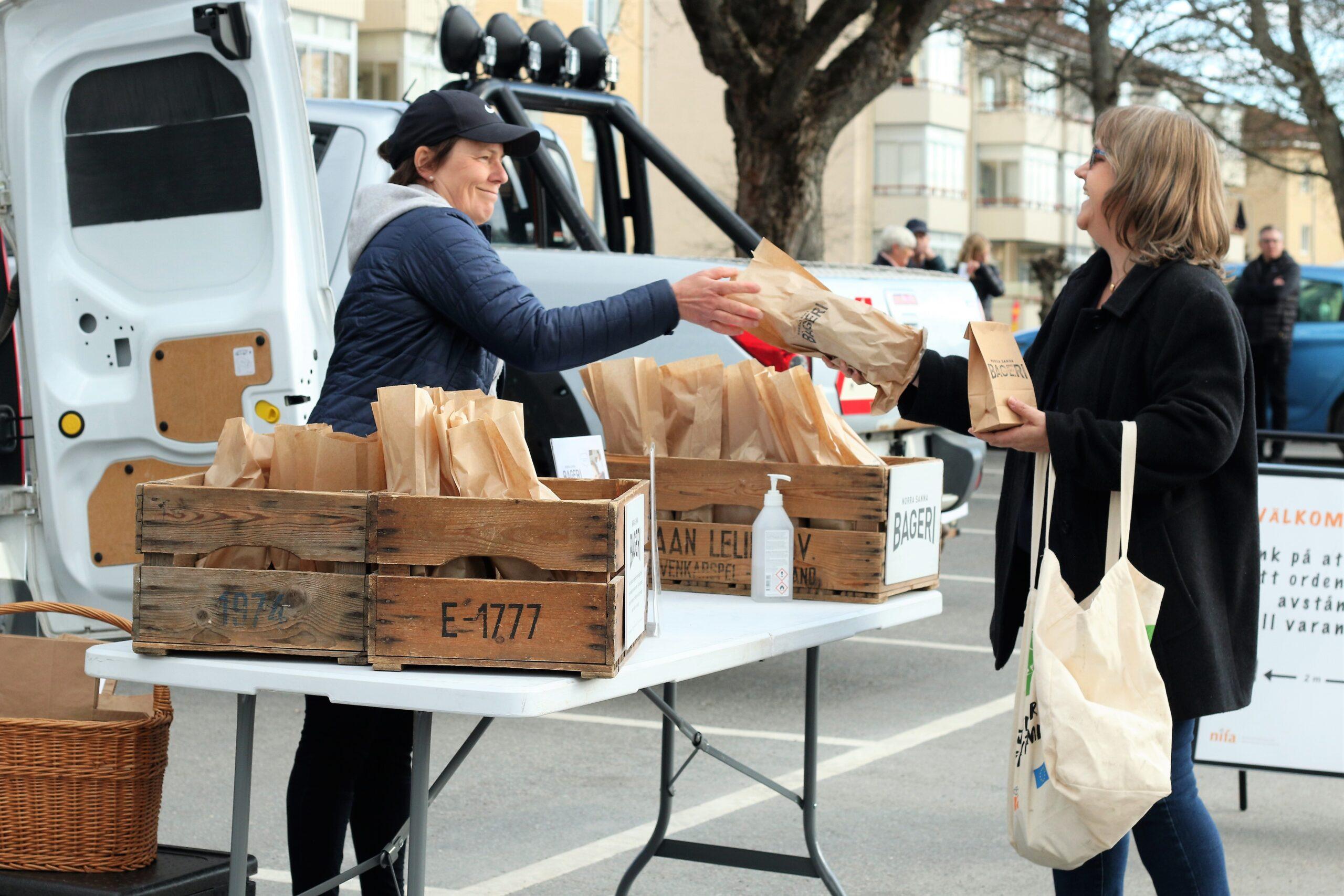 Kvinna säljer bröd till kund utomhus på bilparkering